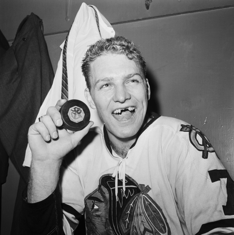 "A legendary ice hockey photo from the 1960s: international star Bobby Hull from the Chicago Blackhawks just scored his 50th goal in one season with this puck. A puck was also responsible for the gaps in his teeth when ""the Golden Jet"" smiled – a badge of honour in ice hockey."