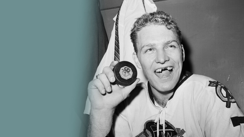 """Legendární hokejová fotografie z šedesátých let minulého století: Bobby Hull, světová hvězda z mužstva Chicago Blackhawks, právě vstřelil tímto pukem svou 50. branku v sezóně. Puk mohl i za ztrátu předních zubů """"zlatého tryskáče"""" – v ledním hokeji představují vyražené zuby věc cti. (Fotografie: Corbis)"""