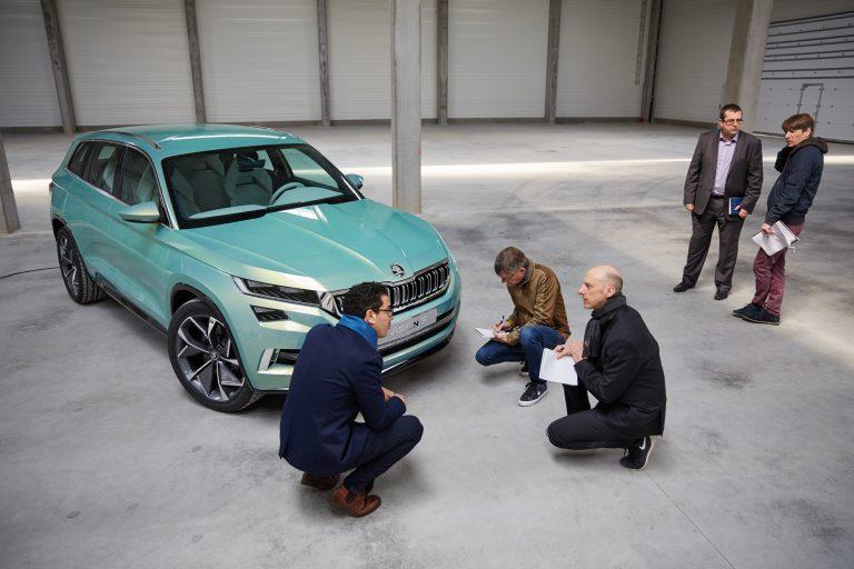 Marwan Khiat (vlevo) vypráví Richardu Bremnerovi (uprostřed) a našemu reportérovi Markovi (vpravo) o mřížce chladiče ze svislých dvojitých žeber, která bude znakem budoucích SUV. Tato je ozdobena českým křišťálovým sklem.