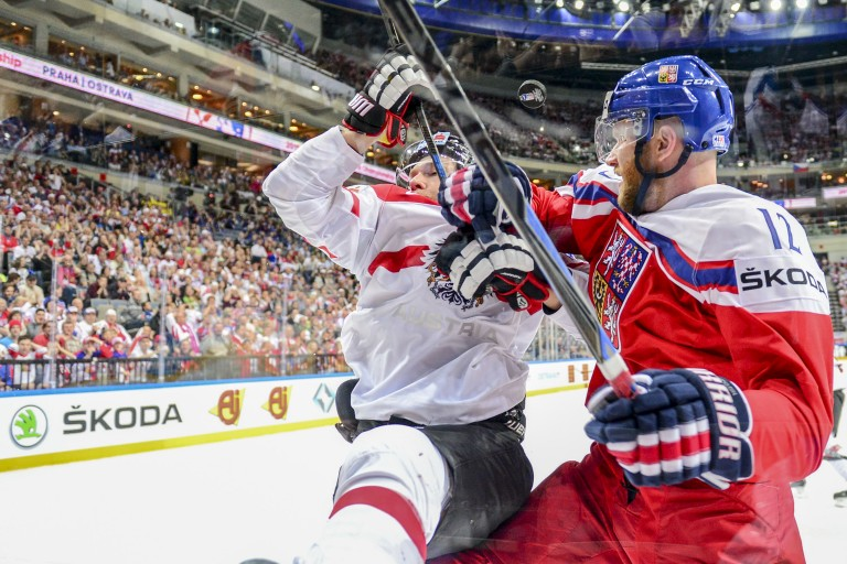 Prominent advertisements for ŠKODA on shirts and perimeters at the Ice Hockey World Cup 2015. The Czech ice hockey star Jiří Novotný (wearing 12) in a duel during the match between Austria and the Czech Republic. The Czech Republic thrashed Austria 4–0.