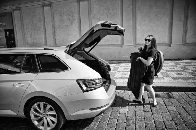 Kateřina pulls her evening dress and horn out of the boot of a ŠKODA SUPERB.