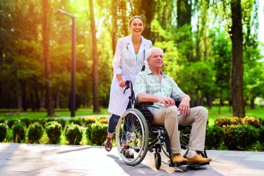 Doctor with old man in wheelchair walking in sunny park