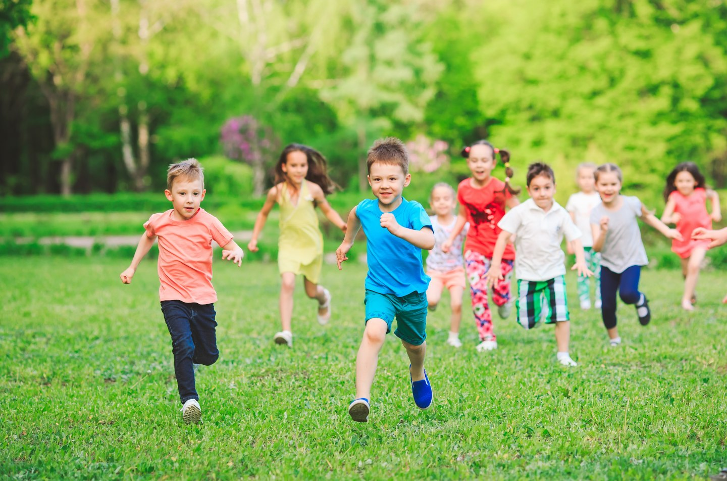 Many different kids, boys and girls running in the park on sunny