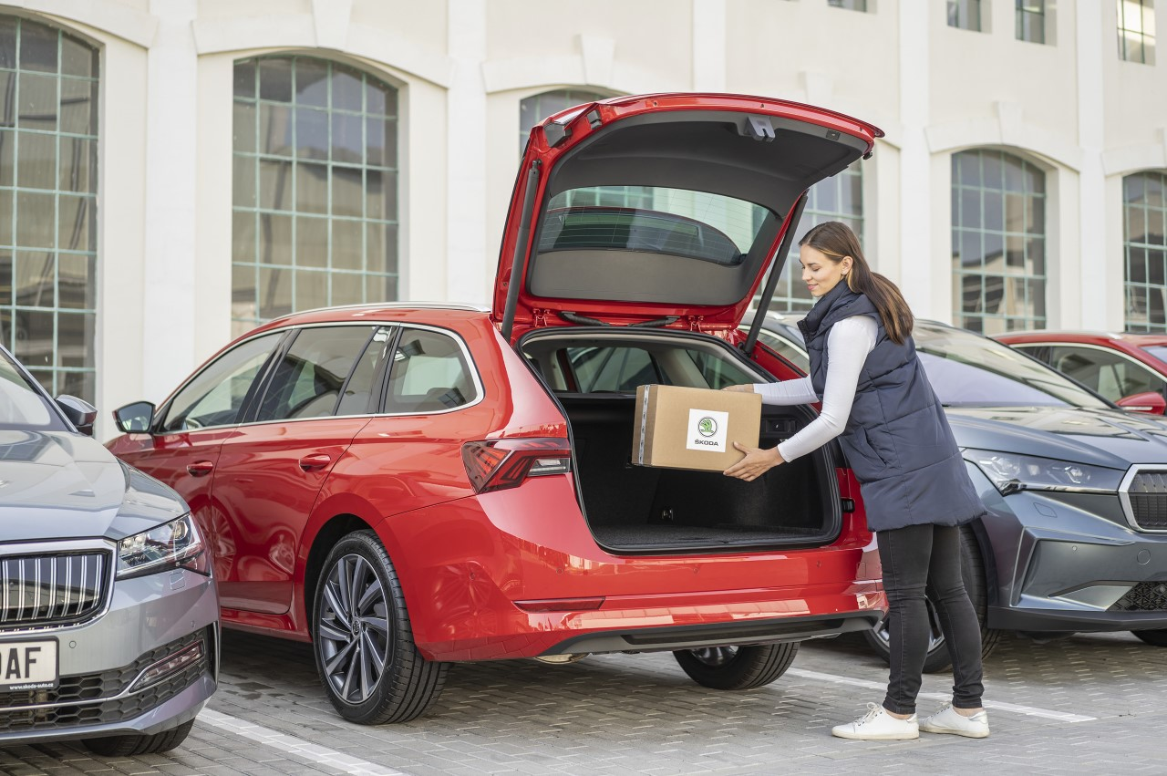 The courier unlocks the car from his app and places the parcel in the trunk.